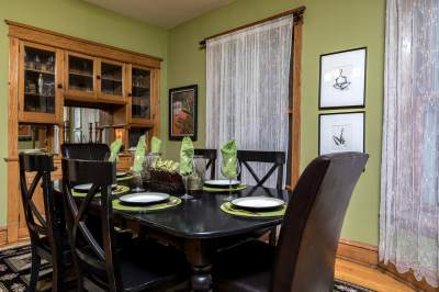 Green dining room with set table