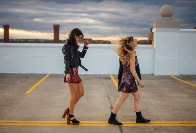 two girls with windblown hair walking on sidewalk