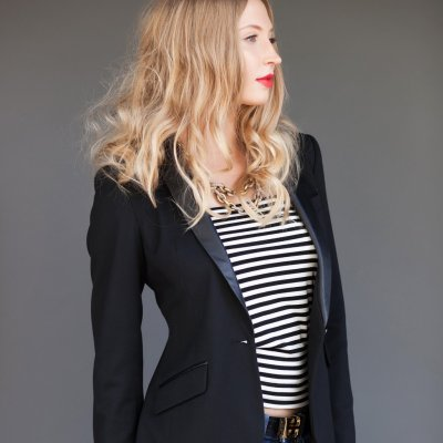 Long haired blonde woman in black blazer with black & white stripped shirt.
