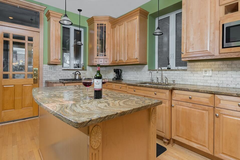 kitchen with green walls and tan cabinets