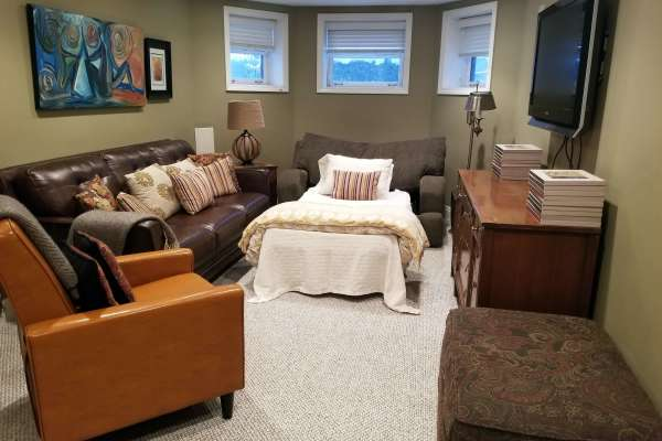 Family room with extra bed with 2 couches, chair and air mattress